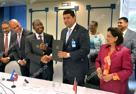 Prime Minister of Trinidad and Tobago Kamla Persad-bissessar (r) Smiles Next to President of Haiti Michel Martelly (2l) Next to Haiti's Minister of Industry and Commerce Wilson Laleau (3l) and Trinidad's Minister of Energy Kevin Ramnarine (2r) Following the Signing of a Memorandum of Understanding Between the Two Countries in Respect of the Sale and Distribution of Petroleum Products Produced by Trinidad and Tobago For Use in Haiti the Signing Followed the Caribbean Community/japan Summit at the Hilton Trinidad and Conference Centre Port-of-spain 28 July 2014 Trinidad and Tobago Port-of-spain