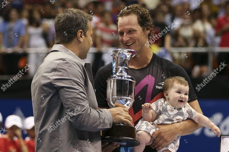 Argentinian David Nalbandian (c) Holds His Daughter As He Receives a Trophy After a Match Against Spanish Rafael Nadal (not Pictured) During an Exhibition Game As Part of the Beggining of Nalbandian's Farewell From Tennis at the Orfeo Stadium in Cordoba Argentina 21 November 2013 Argentina Cordoba