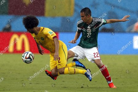 Paul Aguilar (r) of Mexico Tackles Benoit Assou-ekotto of Cameroon During the Fifa World Cup 2014 Group a Preliminary Round Match Between Mexico and Cameroon at the Estadio Arena Das Dunas in Natal Brazil 13 June 2014 (restrictions Apply: Editorial Use Only not Used in Association with Any Commercial Entity - Images Must not Be Used in Any Form of Alert Service Or Push Service of Any Kind Including Via Mobile Alert Services Downloads to Mobile Devices Or Mms Messaging - Images Must Appear As Still Images and Must not Emulate Match Action Video Footage - No Alteration is Made to and No Text Or Image is Superimposed Over Any Published Image Which: (a) Intentionally Obscures Or Removes a Sponsor Identification Image; Or (b) Adds Or Overlays the Commercial Identification of Any Third Party Which is not Officially Associated with the Fifa World Cup) Brazil Natal