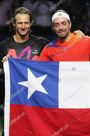Argentinian David Nalbandian (l) and Chilean Nicolas Massu (r) Hold a Chilean Flag During a Farewell Tennis Exhibition For Massu in Santiago De Chile Chile 20 Noviembre De 2013 Massu Says Good-bye to the Field with a Exhibition Game Againts Nalbandian Massu was the Only Player who Won Two Gold Medals in the Olympic Games in Athens 2004 Chile Santiago De Chile