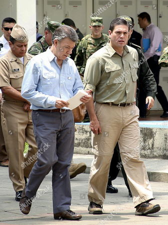 Colombian President Juan Manuel Santos (l) and Colombian Defense Minister Juan Carlos Pinzon (r) Leave a Security Council in Cali Southwest of Colombia 15 April 2015 Colombian President Juan Manuel Santos on 15 April Revived Airstrikes on Rebels of the Revolutionary Armed Forces of Colombia (farc) After 11 Fighters Died in a Clash Santos Had Called Off Airstrikes Against Farc Camps on March 10 But Moved to Relaunch Them After 10 Soldiers and at Least One Rebel Were Killed in a Clash Between the Army and Farc Late 14 April in Southern Colombia 9 Other Soldiers Were Injured Three of Them with Serious Wounds when Their Party was Attacked by Rebels Armed with Rifles Grenades and Explosives Near the Town of Suarez in the Cauca Province Colombia Cali