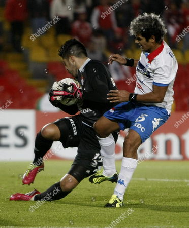 Santa Fe's Goalkeeper Camilo Vargas (l) Holds the Ball As Silvio Torales (r) From Nacional Tries to Score During Their Libertadores Cup Match at El Campin Stadium in Bogota Colombia 11 February 2014 Colombia Bogota