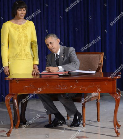 Us President Barack Obama (r) Signing the Guestbook Next to the Prime Minister of Jamaica Portia Simpson-miller (l) During the First Official Act of Obama's Agenda in Kingston Jamaica 09 April 2015 Obama Made an Official Stop in Jamaica Before Travelling to Panama Jamaica Kingston