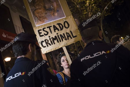 A Demostrator Holds a Banner Reading 'Criminal State' in Front of National Police Officers During a Protest Against the Government's Decision to Withdraw Its Plans to Restrict Abortions Outside the People's Party (pp) Headquarters in Madrid Spain 23 September 2014 Spain's Conservative Government on 23 September Withdrew Its Plans to Restrict Abortions After Months of Protests Against the Proposal From Women's Groups and the Opposition Prime Minister Mariano Rajoy Said the Decision was Made Because the Government was Unable to Achieve a Consensus on the Issue He Had Made a Campaign Promise to Roll Back a 2010 Law Passed by the Then-socialist Government That Allows Abortions Up to the 14th Week of Pregnancy Without Restrictions Rajoy's Government Had Sought to Make Abortion Illegal in Principle with Exceptions in the Case of Rape Or when the Life of the Mother is at Risk After the Government Withdrew the Proposal Justice Minister Alberto Ruiz-gallardon who Had Spearheaded It Announced His Resignation Spain Madrid