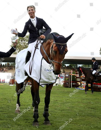 Stock Photo of Us Rider Richard Spooner with His Horse Caretol 2 Poses with the Trophy After Winning the Speed Race During the International Horse Jump Contest Held at Las Mestas' Race Course of Gijon Northern Spain 30 August 2013 Spain Gijon