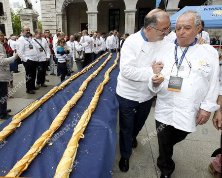 Spanish Chefs Pedro Subijana (2-r) and Juan Mari Arzak (r) Pose Prior to Share out a 300-metre-long Squid Rings Fried in Batter Baguette Among Members of the Public on the Occasion of the Celebration of the National Assembly of Euro-toques at La Magdalena Palace in Santander Northern Spain 12 May 2014 the Chefs Have Gathered to Exchange Information on the Aims of This Organization For the Upcoming Year Euro-toques is the Most Important Chefs' Association in Europe with More Than 3 500 Members in 18 Countries Spain Santander