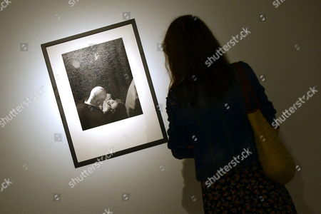 Stock Image of A Woman Looks at a Photo Picturing Aristocrat Justin Portman and His Wife Russian Model Natalia Vodianova As She Visit the Exhibition 'Larry Fink the Vanities Hollywood Parties 2000-2009' in Valladolid Central Spain 29 August 2013 It is the First Time Fink's Work is Displayed in Spain the Exhibition Running From 29 August to 04 November Features Some 100 Photos Taken in Hollywood Spain Valladolid