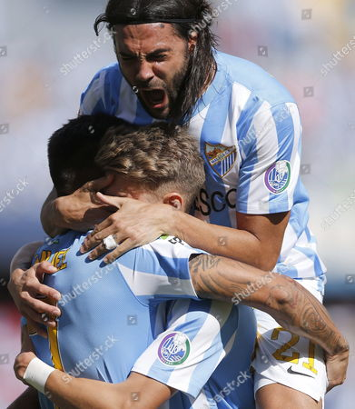 Fc Malaga's Defender Sergio Sanchez (top) Celebrates with Team Mates Samuel Garcia (l) and Samel Castillejo (r) After Scoring Against Rayo Vallecano During Their Spanish First Division League Soccer Match at La Rosaleda Stadium in Malaga South-eastern Spain 26 October 2014 Spain Malaga