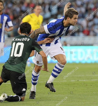 Krasnodar's Midfielder Odil Ahmedov (l) Fights For the Ball with Defender Carlos Martinez (r) of Real Sociedad During the Uefa Europa League First Leg Play-off Match Between Real Sociedad and Krasnodar Played at Anoeta Stadium in San Sebastian Basque Country Spain on 21 August 2014 Spain San Sebastißn