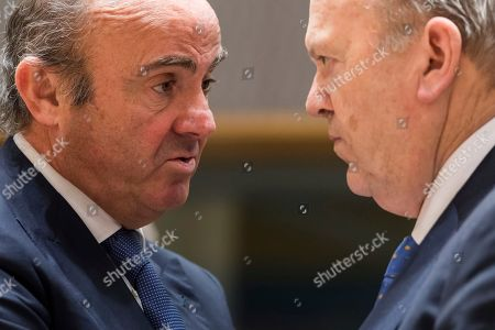 Spain's Finance Minister Luis de Guindos, left, talks with Ireland's Finance Minister Michael Noonan during a round table meeting of eurozone finance ministers at the EU Council building in Brussels on