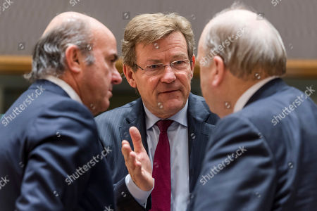 Belgium's Finance Minister Johan Van Overtveldt, centre, talks with Spain's Finance Minister Luis de Guindos, left, and Ireland's Finance Minister Michael Noonan during a round table meeting of eurozone finance ministers at the EU Council building in Brussels on