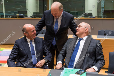 Spain's Finance Minister Luis de Guindos, left, talks with France's Finance Minister Michel Sapin, right, and Ireland's Finance Minister Michael Noonan during a round table meeting of eurozone finance ministers at the EU Council building in Brussels on