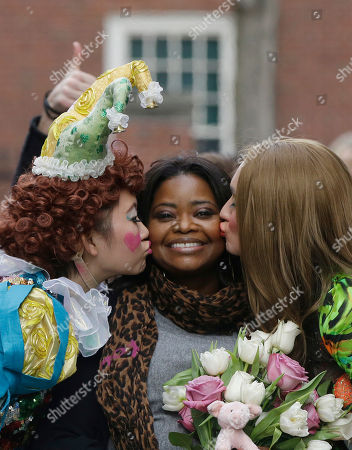 Guan-Yue Chen, Hasty Pudding Theatricals President, left, and Dan Milashewski, vice president, kiss actress Octavia Spencer during a parade to honor Spencer as the Hasty Pudding Theatricals Woman of the Year, in Cambridge, Mass