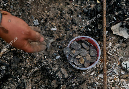 Claudia Salinas picks up charred coins, which belong to her daughter, in what remains of their home destroyed by fire in Santa Olga, Chile, . Officials say the town was consumed by the country's worst wildfires, engulfing the post office, a kindergarten and hundreds of homes