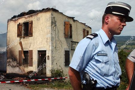 A Policeman Stands in Front Pf a Horseback Riding School in the Village of Lescheraines in the Savoie Region North of Chambery Eastern France Thursday August 5 2004 Up to Nine People Including Seven Teenagers Died in the Incident Dozens of Firefighters Rushed to the Scene After the Fire Swept Through a Building where the Victims Were Sleeping the Teenagers Between 13 and 15 Years Old Were From the Region But Stayed Overnight at School Sports Minister Jean-francois Lamour Said Two Adults Were Believed Dead As Well Though Investigations Were Still Continuing France Lescheraines
