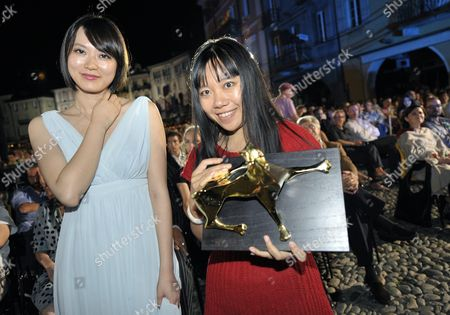 Chinese Director Xiaolu Guo Right and Actress Huang Lu Left Pose with the Golden Leopard the Top-ranking Award of the International Competition They Recieved For Their Movie 'She a Chinese' After the Award Ceremony on Piazza Grande at the 62nd Locarno International Film Festival Saturday August 15 2009 in Locarno Switzerland Switzerland Schweiz Suisse Locarno