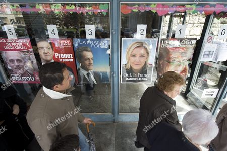 French People Living in Switzerland Walk in Front of Placards Showing Candidates Philippe Poutou Jean-luc Melanchon French President Nicolas Sarkozy Marine Le Pen and Eva Joly (l-r) Outside a Polling Station For the First Round of the French Presidential Election in Lausanne Switzerland 22 April 2012 Reports State That Some 120 000 French Citizens in Switzerland Are Registered to Vote in the French Presidential Election Switzerland Schweiz Suisse Lausanne