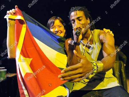 Member of Cuban Hip Hop Band 'Orishas' Singer Yotuel Romero Performs on Stage As a Fan Holds a Cuban Flag at the Avo Session in Basel Switzerland 30 October 2009 Switzerland Schweiz Suisse Basel