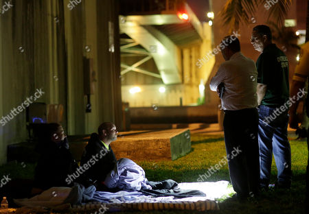 Ron Book, chairman of the Homeless Trust, center, talks with a homeless man during the annual Point-in-Time count of the homeless in Miami-Dade County, in Miami. The count is mandated by the U.S. Department of Housing and Urban Development to help communities track progress toward the goal of ending homelessness