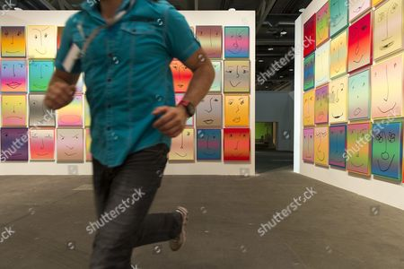A Man Runs Trough the Exhibition Hall As a Part of the Performance by British Artist Martin Creed in Front of 'Us' (2013) by Us Artist Rob Pruitt Represented by the Gallery Brown (new York) at the Exhibition Art Unlimited in the Context of the International Art Show Art Basel in Basel Switzerland 11 June 2013 Unlimited is Art Basel's Exhibition Platform For Projects That Transcend the Limitations of a Classical Art-show Stand Including Out-sized Sculpture and Paintings Video Projections Large-scale Installations and Live Performances the International Art Fair Art Basel Opens to the Public From 13 to 16 June Switzerland Schweiz Suisse Basel