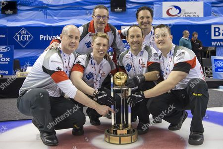 Canada's Skip Kevin Koe Third Marc Kennedy Second Brent Laing Lead Ben Hebert Front From Left Coach John Dunn and Alternate Scott Pfeifer Back From Left Present the Trophy After Winning the Gold Medal Game Against Denmark at the World Men's Curling Championship 2016 in the St Jakobshalle in Basel Switzerland on Sunday April 10 2016 Switzerland Schweiz Suisse Basel