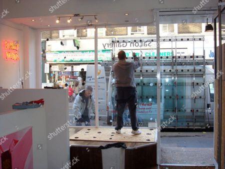 Workmen repair smashed windows