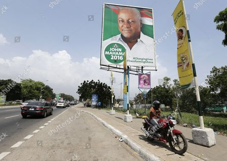 A Ghanaian Motorcyclist Rides in Front of a Presidential Campaign Billboard For Incumbent President John Mahama in Accra Ghana 12 November 2016 the General Presidential and Parliamentary Elections in Ghana Will Be Held on 07 December 2016 Ghana Accra