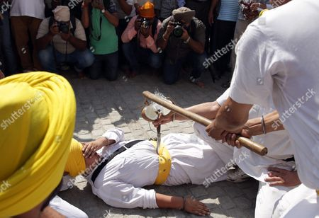 Stock Photo of Journalists Take Pictures As a Sikh Man Breaks a Cocunut Kept on a Mini Sword on Another Man's Stomach As They Performing 'Gatka' an Ancient Form of Sikh Martial Art During a Religious Procession in Amritsar India 15 October 2016 on the Eve of the 482nd Birth Anniversary of the Fourth Guru Or the Master of the Sikhs Sri Guru Ramdas Ji Sri Guru Ramdas Ji Also Established the City of Amritsar the Birth Anniversary of the Fourth Sikh Guru is One of the Major Religious Events For Sikh Community Especially For the People of Amritsar India Amritsar