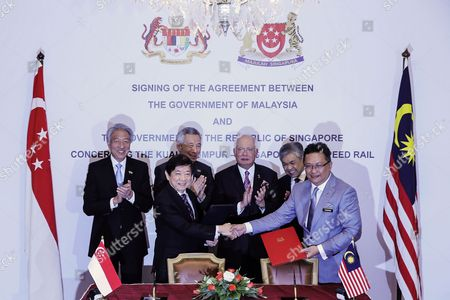 Malaysia Prime Minister Najib Razak (c-r) and Singapore Prime Minister Lee Hsien Loong (back 3-l) Look on After Minister in the Prime Minister's Department of Malaysia Abdul Rahman Dahlan (r) and Singapore Transport Minister Khaw Boon Wan (2-l) Sign a Bilateral Agreement on a High-speed Rail Project Between Kuala Lumpur and Singapore at the Malaysia Prime Minister's Office in Putrajaya Malaysia 13 December 2016 Malaysia Putrajaya