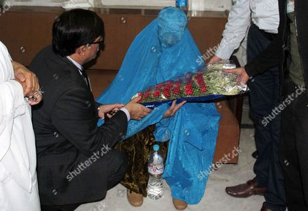 A Lawyer Presents a Boquet to Afghan Refugee Woman Sharbat Gula (c in Burqa) As She was Deported to Afghanistan in Peshawar Pakistan Early 09 November 2016 Pakistani Anti-corruption and Immigration Court Had on 04 November Has Handed a 15-days Jail and 110000 Pak Rupees (1000 Us Dollar) Fine to Sharbat Gula Before Being Deported to Afghanistan Gula Has Been Detained For Allegedly Possessing a Fake Identity Card She was Arrested on 26 October For Allegedly Obtaining Pakistani Identity Documents For Herself and Her Two Children After Bribing Three Officials Charges That Could Land Her a 14-year Jail Sentence Sharbat Gula Became Famous by the Photographic Portrait 'Afghan Girl' Taken of Her with Her Striking Green Eyes by Photographer Steve Mccurry and Published on the Cover of the 'National Geographic' in June 1985 Pakistan Peshawar