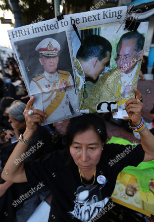 A Thai Well-wisher Holds Up Portraits of Thai Crown Prince Maha Vajiralongkorn (l) and His Father Late Thai King Bhumibol Adulyadej (r) As They Gather Outside the Grand Palace in Bangkok Thailand 01 December 2016 the Buddhist Monks of All Thai Temples in the World Will Pray For the Crown Prince Maha Vajiralongkorn 64 Ascending the Throne As the 10th King of the Chakri Dynasty by the Formally Invitation of Thailand's National Legislative Assembly (nla) and the Heads of Country Executive on 01 December 2016 the Prince is Due to Succeed His Father Late Thai King Bhumibol Adulyadej the World's Longest Reigning Monarch who Died at the Age of 88 in Siriraj Hospital on 13 October 2016 Thailand Bangkok