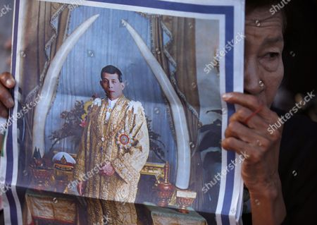 A Thai Well-wisher Holds Up a Portrait of Thai Crown Prince Maha Vajiralongkorn on the Front Page of the Newspaper As They Gather Outside the Grand Palace in Bangkok Thailand 01 December 2016 the Buddhist Monks of All Thai Temples in the World Will Pray For the Crown Prince Maha Vajiralongkorn 64 Ascending the Throne As the 10th King of the Chakri Dynasty by the Formally Invitation of Thailand's National Legislative Assembly (nla) and the Heads of Country Executive on 01 December 2016 the Prince is Due to Succeed His Father Late Thai King Bhumibol Adulyadej the World's Longest Reigning Monarch who Died at the Age of 88 in Siriraj Hospital on 13 October 2016 Thailand Bangkok