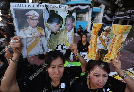 Stock Picture of Thai Well-wishers Hold Up Portraits of Thai Crown Prince Maha Vajiralongkorn and His Father Late Thai King Bhumibol Adulyadej (c) As They Gather Outside the Grand Palace in Bangkok Thailand 01 December 2016 the Buddhist Monks of All Thai Temples in the World Will Pray For the Crown Prince Maha Vajiralongkorn 64 Ascending the Throne As the 10th King of the Chakri Dynasty by the Formally Invitation of Thailand's National Legislative Assembly (nla) and the Heads of Country Executive on 01 December 2016 the Prince is Due to Succeed His Father Late Thai King Bhumibol Adulyadej the World's Longest Reigning Monarch who Died at the Age of 88 in Siriraj Hospital on 13 October 2016 Thailand Bangkok