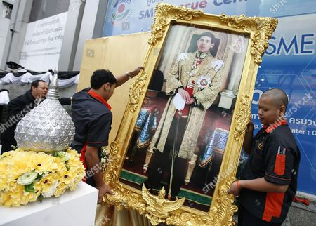 Stock Image of Thai Workers Place a Large a Portrait of King Maha Vajiralongkorn Bodindradebayavarangkun (king Rama X) to Be Displayed in Observance of the Accession of Newly Proclaimed King Rama X to the Throne in Front of the Sme Bank Building in Bangkok Thailand 02 December 2016 Thailand Has New King After Crown Prince Maha Vajiralongkorn 64 Accepted to Ascend the Throne to Become the Country's New Monarch the 10th King of the 234-year-old Chakri Dynasty on 01 December 2016 the King Maha Vajiralongkorn Bodindradebayavarangkun Succeeds His Late Father Thai King Bhumibol Adulyadej the World's Longest Reigning Monarch who Died at the Age of 88 in Siriraj Hospital on 13 October 2016 Thailand Bangkok