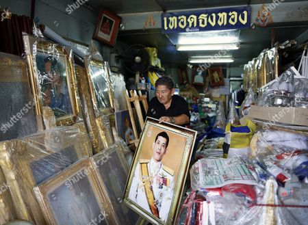 A Thai Shop Owner Carries a Framed Photograph of Thai Crown Prince Maha Vajiralongkorn at a Royal Authorized Memorabilia Shop in Bangkok Thailand 29 November 2016 Thailand's National Legislative Assembly (nla) Invited Crown Prince Maha Vajiralongkorn 64 to Become the Country's New Monarch the 10th King of the Chakri Dynasty on 29 November 2016 the Prince is Due to Succeed His Father Late Thai King Bhumibol Adulyadej the World's Longest Reigning Monarch who Died at the Age of 88 in Siriraj Hospital on 13 October 2016 Thailand Bangkok