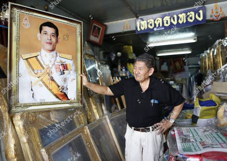 A Thai Shop Owner Adjusts a Framed Photograph of Thai Crown Prince Maha Vajiralongkorn at a Royal Authorized Memorabilia Shop in Bangkok Thailand 29 November 2016 Thailand's National Legislative Assembly (nla) Invited Crown Prince Maha Vajiralongkorn 64 to Become the Country's New Monarch the 10th King of the Chakri Dynasty on 29 November 2016 the Prince is Due to Succeed His Father Late Thai King Bhumibol Adulyadej the World's Longest Reigning Monarch who Died at the Age of 88 in Siriraj Hospital on 13 October 2016 Thailand Bangkok
