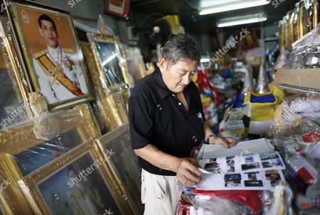 A Thai Shop Owner Checks a Catalog Book Next to a Framed Photograph of Thai Crown Prince Maha Vajiralongkorn who Succeed the Throne at a Shop in Bangkok Thailand 29 November 2016 Thailand's National Legislative Assembly (nla) Invited Crown Prince Maha Vajiralongkorn 64 to Become the Country's New Monarch the 10th King of the Chakri Dynasty on 29 November 2016 the Prince is Due to Succeed His Father Late Thai King Bhumibol Adulyadej the World's Longest Reigning Monarch who Died at the Age of 88 in Siriraj Hospital on 13 October 2016 Thailand Bangkok