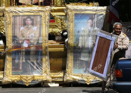 A Thai Official Carries a Purchased Framed Photograph Next to Portraits of Thai Crown Prince Maha Vajiralongkorn (l) and Late Thai King Bhumibol Adulyadej (r) at a Royal Authorized Memorabilia Shop in Bangkok Thailand 29 November 2016 Thailand's National Legislative Assembly (nla) Invited Crown Prince Maha Vajiralongkorn 64 to Become the Country's New Monarch the 10th King of the Chakri Dynasty on 29 November 2016 the Prince is Due to Succeed His Father Late Thai King Bhumibol Adulyadej the World's Longest Reigning Monarch who Died at the Age of 88 in Siriraj Hospital on 13 October 2016 Thailand Bangkok