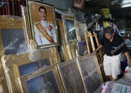 A Thai Shop Owner Adjusts Framed Photographs of Thai Crown Prince Maha Vajiralongkorn Along with Portraits of Late Thai King Bhumibol Adulyadej at a Royal Authorized Memorabilia Shop in Bangkok Thailand 29 November 2016 Thailand's National Legislative Assembly (nla) Invited Crown Prince Maha Vajiralongkorn 64 to Become the Country's New Monarch the 10th King of the Chakri Dynasty on 29 November 2016 the Prince is Due to Succeed His Father Late Thai King Bhumibol Adulyadej the World's Longest Reigning Monarch who Died at the Age of 88 in Siriraj Hospital on 13 October 2016 Thailand Bangkok