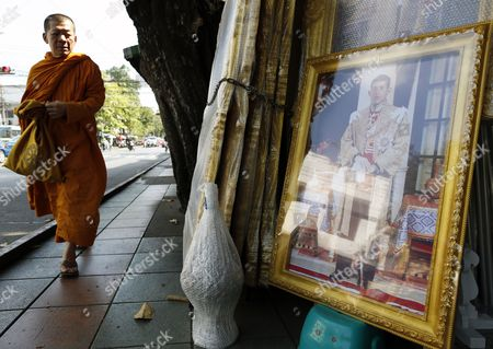 A Thai Buddhist Monk Walks Next to a Framed Photograph of Thai Crown Prince Maha Vajiralongkorn at a Royal Authorized Memorabilia Shop in Bangkok Thailand 29 November 2016 Thailand's National Legislative Assembly (nla) Invited Crown Prince Maha Vajiralongkorn 64 to Become the Country's New Monarch the 10th King of the Chakri Dynasty on 29 November 2016 the Prince is Due to Succeed His Father Late Thai King Bhumibol Adulyadej the World's Longest Reigning Monarch who Died at the Age of 88 in Siriraj Hospital on 13 October 2016 Thailand Bangkok