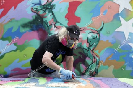 Street Artist Ron English of the Us Touches Up a Rock in Front of His Mural in the Wynwood District During Art Basel in Miami Florida Usa 01 December 2016 Art Galleries and Artists From All Over the World Descend on Miami For the Event Which is Considered One of the World's Largest Art Festivals with Art Events Throughout the City United States Miami