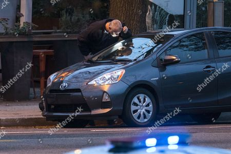 An Investigator Examines a Car Outside Comet Ping Pong a Pizza Restaurant That was the Subject of a Fake News Story Claiming It was the Center of a Child Sex Ring Orchestrated by Hillary Clinton and Her Campaign Chief John Podesta After a Man with an Assault Rifle Entered the Restaurant in Washington Dc Usa 04 December 2016 the Popular Neighborhood Restaurant Along with Its Employees Have Endured Weeks of Threats Since the Fake News Story Referred to As 'Pizzagate' Began Appearing on Websites United States Washington