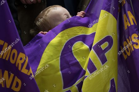 Three-year-old David Walker from Ambleside peeks over the top of a UKIP flag during a visit by Paul Nuttall and candidate Fiona Mills with deputy leader Peter Whittle AM at  the constituency of Copeland to launch the party's by-election office