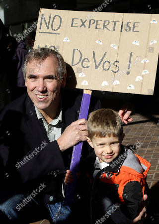 Stock Photo of Jeff Merkley, Asher Kockler Sen. Jeff Merkley, D-Ore., left, poses with Asher Kockler and his sign for a family member during a rally in Portland, Ore., . Several hundred supporters gathered with Oregon congressional leaders in protest against Education Secretary nominee Betsy DeVos