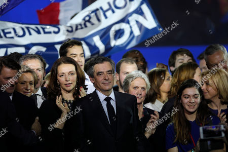 Conservative presidential candidate Francois Fillon smiles with aide Valerie Boyer, center left, and his wife Penelope, center right, after a campaign meeting in Paris, . Financial prosecutors are investigating an allegedly fake but handsomely paid job held by the Fillon's wife, Penelope