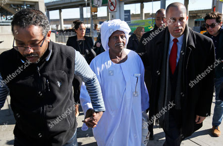 Yassin Abdelrhman, center, of Sudan, is escorted out of John F. Kennedy Airport by his son, Ali Suliman, left, and Congressman Hakeem Jeffries, in New York, . Attorneys advocating on his behalf said he is a lawful permanent resident and was held at the airport for more than 24 hours