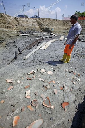 A Man Stands at the Ostia Antica Archaeological Site in Rome Italy where an Ancient Roman Ship Has Been Discovered on 28 April 2011 an Ancient Ship Has Emerged From the Ground at the Imperial Roman Port of Ostia in a Find Culture Minister Giancarlo Galan Said 'Gives You Goose Bumps' an 11-metre Section of One of the Ship's Sides Has So Far Been Discovered Archaeologists Said They and Galan Said the Discovery Would Make Experts Think Anew About the Exact Location of the Port where the Roman Empire's Biggest Fleet was Stationed and Through Which Goods Travelled to and From the Imperial Capital Italy Rome