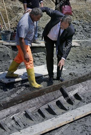 Italian Culture Minister Giancarlo Galan (r) is Pictured at the Ostia Antica Archaeological Site in Rome Italy where an Ancient Roman Ship Has Been Discovered on 28 April 2011 an Ancient Ship Has Emerged From the Ground at the Imperial Roman Port of Ostia in a Find Culture Minister Giancarlo Galan Said 'Gives You Goose Bumps' an 11-metre Section of One of the Ship's Sides Has So Far Been Discovered Archaeologists Said They and Galan Said the Discovery Would Make Experts Think Anew About the Exact Location of the Port where the Roman Empire's Biggest Fleet was Stationed and Through Which Goods Travelled to and From the Imperial Capital Italy Rome