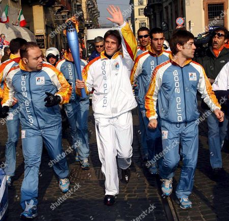 Emmanuele Filiberto of Savoy (c) the Son of Savoy's Prince Vittorio Emanuele Waves As He Carries the Olympic Torch Thursday 09 February 2006 in Turin the Winter Olympic Games Will Be Opened Tomorrow Friday February 10 2006 Italy Turin