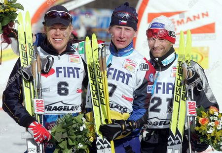 (l-r) Sweden's Mathias Fredriksson Second Placed Chech Lukas Bauer First Placed and Norway's Kristen Skjeldal Third Placed Celebrate on the Podium After the Men's 'Viessmann' World Cup Cross-country Competition in Pragelato (italy) on Saturday 22 January 2005 Italy Pragelato (italy)
